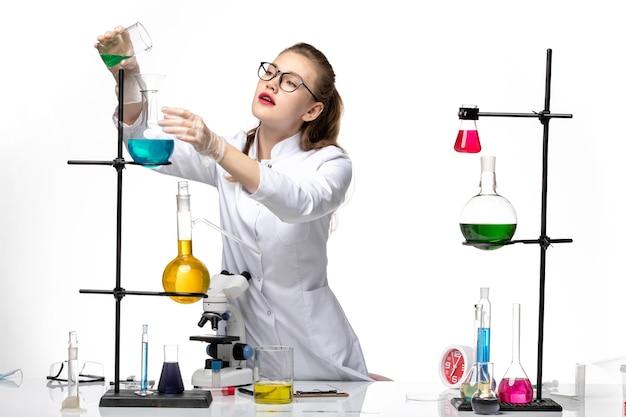 Vooraanzicht vrouwelijke chemicus in medisch pak in werkproces met oplossingen op witte achtergrond chemie pandemisch covid-virus