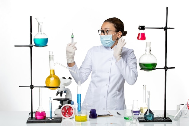 Vooraanzicht vrouwelijke chemicus in medisch pak met injectie van de maskerholding op witte achtergrond het laboratoriumcovidplons van het viruschemie