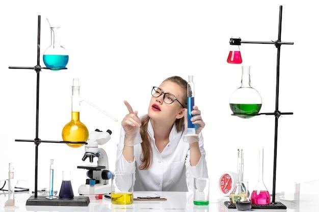Vooraanzicht vrouwelijke chemicus in medisch pak met lange kolf met blauwe oplossing op witte achtergrond chemie pandemie gezondheid covid