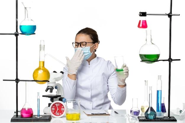 Vooraanzicht vrouwelijke chemicus in medisch pak met masker drinken oplossing op witte achtergrond splash lab virus chemie covid
