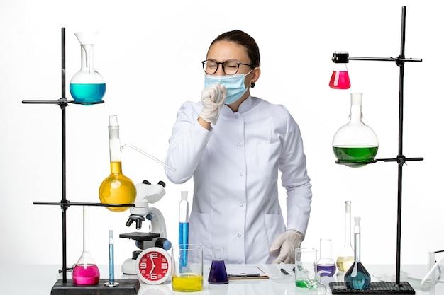 Vooraanzicht vrouwelijke chemicus in medisch pak met masker hoesten op witte achtergrond virus chemie lab covid-splash