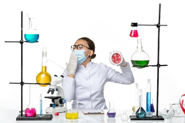 Vooraanzicht vrouwelijke chemicus in medisch pak met masker houden klokken geeuwen op de witte achtergrond virus lab chemie covid-splash