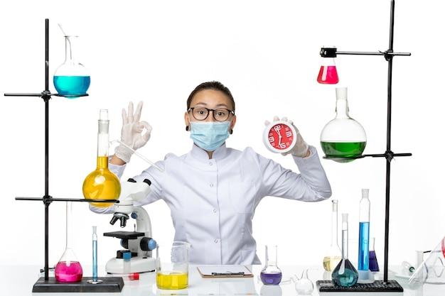 Vooraanzicht vrouwelijke chemicus in medisch pak met masker houden klokken op witte achtergrond virus lab chemie covid splash