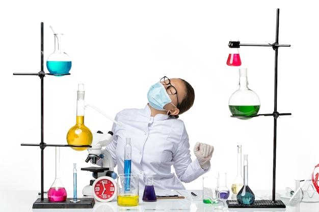 Vooraanzicht vrouwelijke chemicus in medisch pak met masker in pijn op witte achtergrond virus chemie lab covid splash