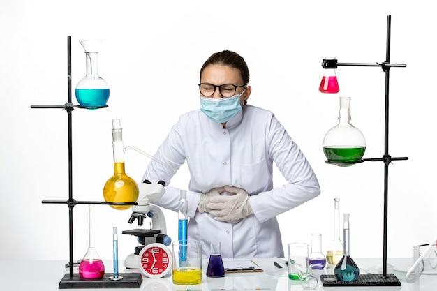 Vooraanzicht vrouwelijke chemicus in medisch pak met masker met buikpijn op witte achtergrond virus chemie lab covid-splash