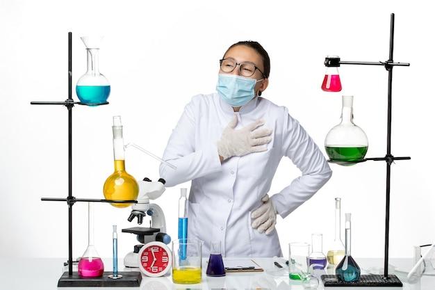 Vooraanzicht vrouwelijke chemicus in medisch pak met masker met hartzeer op witte achtergrond virus chemie lab covid-splash