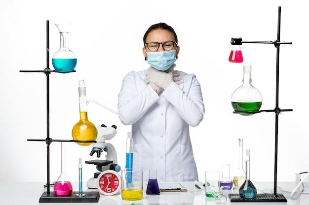 Vooraanzicht vrouwelijke chemicus in medisch pak met masker met keelpijn op witte achtergrond virus chemie lab covid-splash