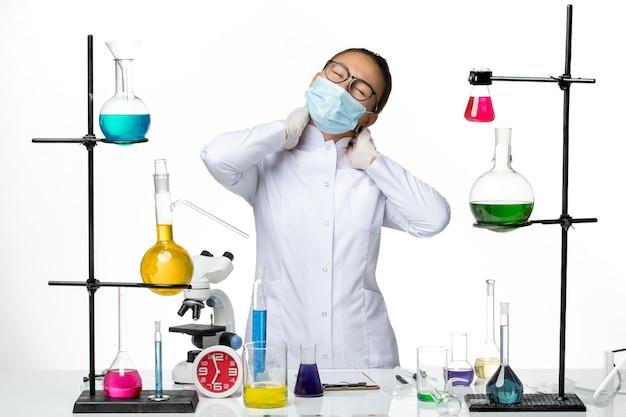 Vooraanzicht vrouwelijke chemicus in medisch pak met masker met nekpijn op witte achtergrond virus chemie lab covid-splash
