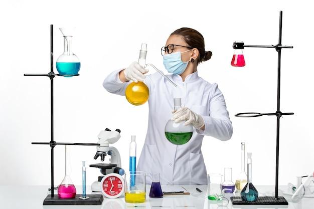Vooraanzicht vrouwelijke chemicus in medisch pak met masker werken met oplossingen op lichte witte achtergrond virus chemie lab covid splash