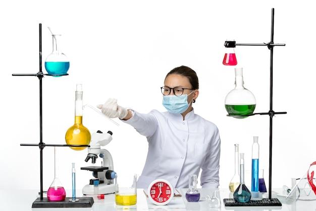 Vooraanzicht vrouwelijke chemicus in medisch pak met masker zittend met oplossingen op lichte witte achtergrond chemie lab virus covid-splash