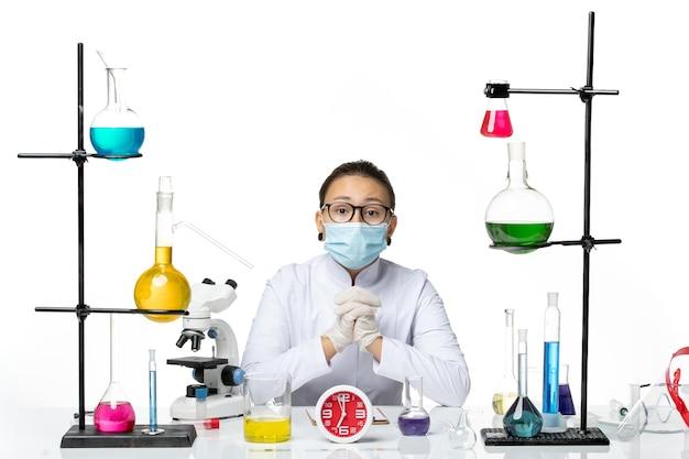 Vooraanzicht vrouwelijke chemicus in medisch pak met masker zittend met oplossingen op wit bureau virus lab chemie covid splash