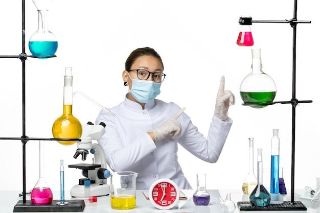 Vooraanzicht vrouwelijke chemicus in medisch pak met masker zittend met oplossingen wijzend op iets op lichte witte achtergrond chemie virus covid-splash
