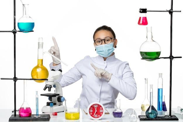 Vooraanzicht vrouwelijke chemicus in medisch pak met maskerzitting met oplossingen op lichte witte achtergrond chemievirus covid-splash