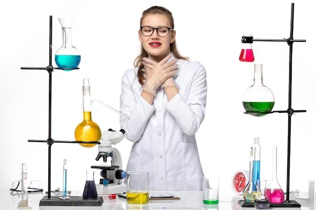 Vooraanzicht vrouwelijke chemicus in medisch pak poseren op wit bureau chemie virus pandemie covid-