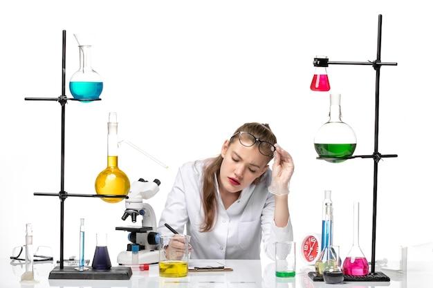 Vooraanzicht vrouwelijke chemicus in medisch pak schrijven van notities op witte achtergrond chemie pandemie gezondheid covid
