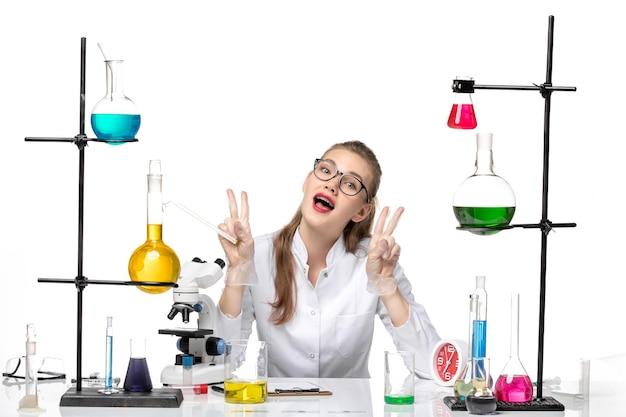 Vooraanzicht vrouwelijke chemicus in medisch pak voor lijst met oplossingen op witte achtergrond pandemische chemie covid-virus