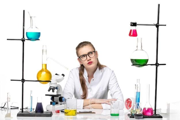 Vooraanzicht vrouwelijke chemicus in medisch pak voor tafel met oplossingen op lichte witte achtergrond pandemische chemie covid-virus
