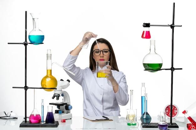 Vooraanzicht vrouwelijke chemicus in medisch pak werken met oplossingen op lichte witte achtergrond lab virus covid-pandemische wetenschap