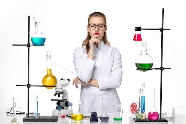 Vooraanzicht vrouwelijke chemicus in medisch pak werken met verschillende oplossingen en denken op witte achtergrond chemie pandemisch covid-virus