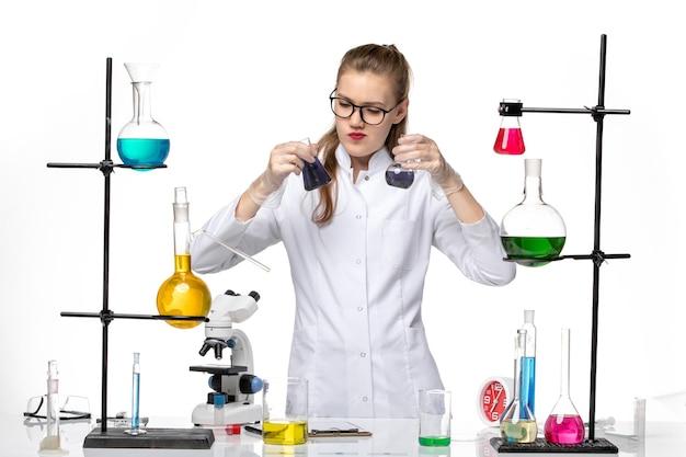 Vooraanzicht vrouwelijke chemicus in medisch pak werken met verschillende oplossingen op witte achtergrond chemie pandemisch covid-virus