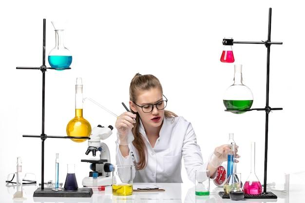 Vooraanzicht vrouwelijke chemicus in medische pak bedrijf kolf op witte achtergrond chemie pandemie gezondheid covid