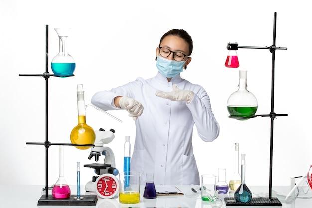 Vooraanzicht vrouwelijke chemicus in medische pak dragen masker kijken naar haar pols op witte achtergrond virus chemie lab covid splash