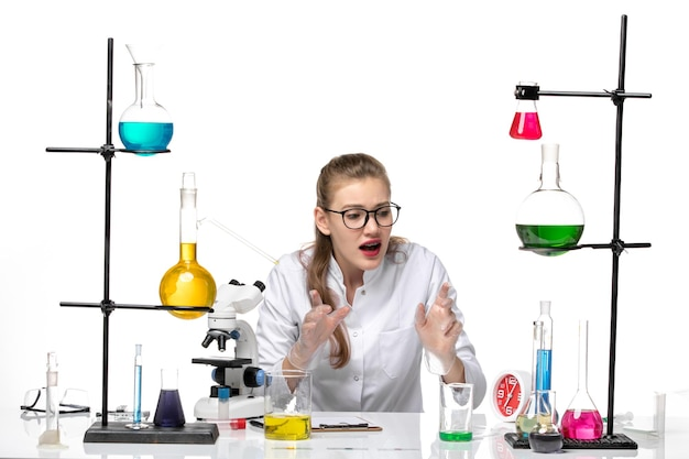 Vooraanzicht vrouwelijke chemicus in medische pak zittend met oplossingen op lichte witte achtergrond pandemische chemie covid-virus