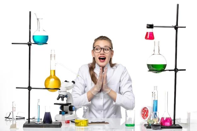 Vooraanzicht vrouwelijke chemicus in medische pak zittend met oplossingen op wit bureau chemie pandemisch covid-virus