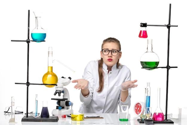 Vooraanzicht vrouwelijke chemicus in medische pak zittend met oplossingen op witte achtergrond pandemische chemie covid-virus