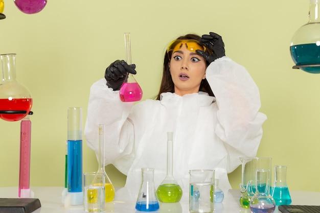 Vooraanzicht vrouwelijke chemicus in speciaal beschermend pak bedrijf kolf met roze oplossing op het lichtgroene oppervlak