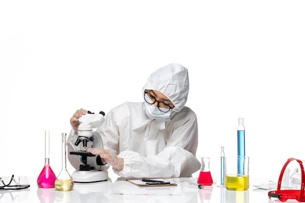 Vooraanzicht vrouwelijke chemicus in speciaal beschermend pak die steekproef controleren op witte achtergrond chemie covid-pandemisch gezondheidsvirus