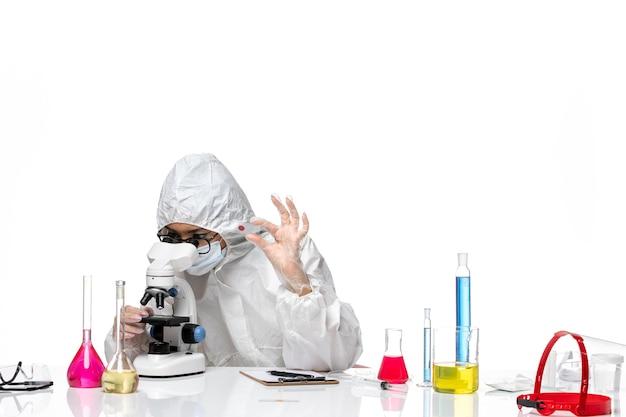Vooraanzicht vrouwelijke chemicus in speciaal beschermend pak die steekproeven op witte achtergrond controleert virus chemie covid-pandemische gezondheid