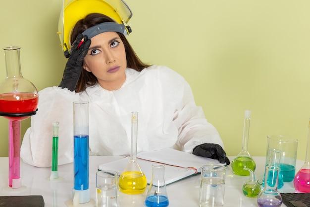 Vooraanzicht vrouwelijke chemicus in speciaal beschermend pak werken met oplossingen en denken aan het groene oppervlak