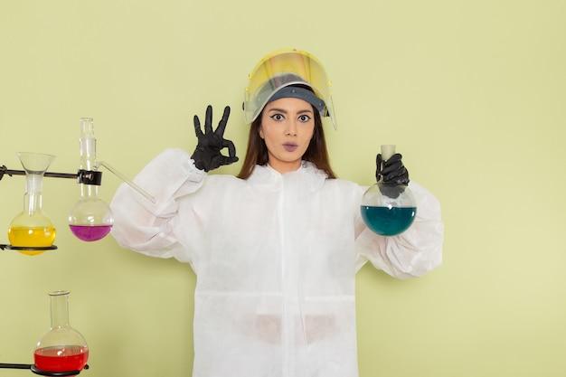 Vooraanzicht vrouwelijke chemicus in speciaal beschermend pak werken met oplossingen op groen bureau
