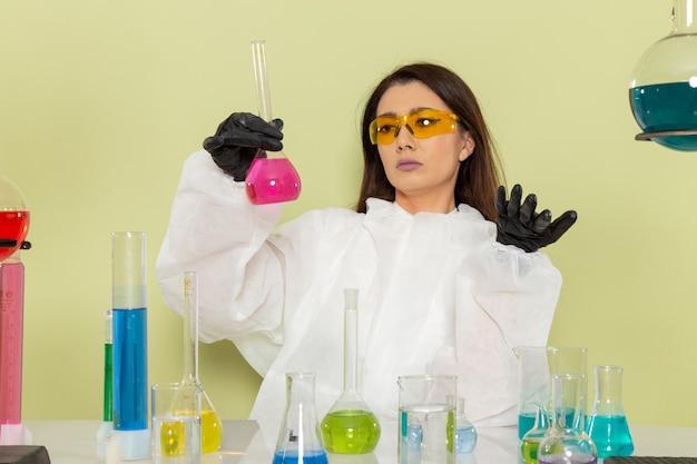 Vooraanzicht vrouwelijke chemicus in speciaal beschermend pak werken met oplossingen op het groene oppervlak
