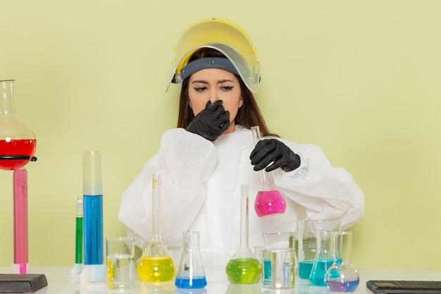 Vooraanzicht vrouwelijke chemicus in speciaal beschermend pak werken met verschillende oplossingen op groen bureau