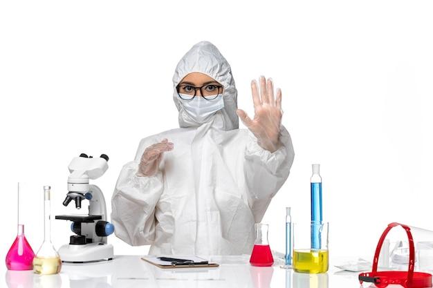 Vooraanzicht vrouwelijke chemicus in speciaal beschermend pak zittend met oplossingen op witte achtergrond chemie pandemisch covid-virus