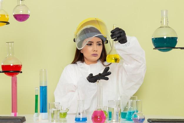 Vooraanzicht vrouwelijke chemicus in speciale beschermend pak houden kolf met gele oplossing op lichtgroen oppervlak
