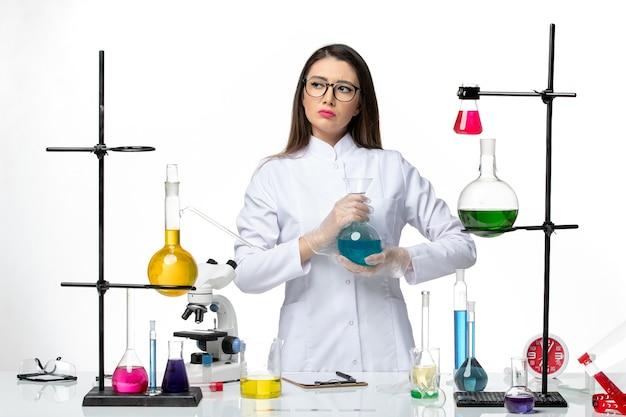 Vooraanzicht vrouwelijke chemicus in steriel medisch pak bedrijf kolf met oplossing op lichte witte achtergrond virus covid- pandemie wetenschap