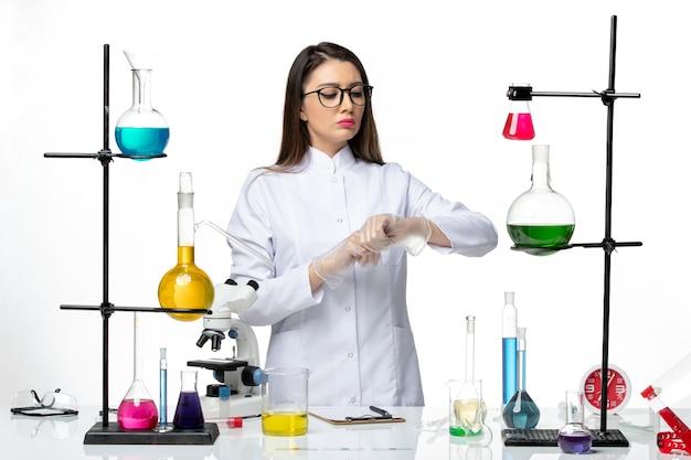 Vooraanzicht vrouwelijke chemicus in steriel medisch pak kijkend naar haar pols op de lichte witte achtergrond virus covid-pandemie wetenschap
