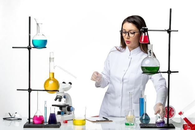 Vooraanzicht vrouwelijke chemicus in steriel medisch pak staande rond tafel met oplossingen op lichte witte achtergrond virusziekte covid- pandemische wetenschap