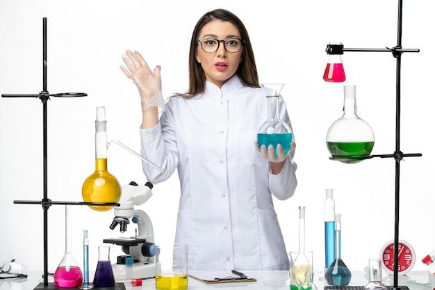 Vooraanzicht vrouwelijke chemicus in steriel medisch pak werken met verschillende oplossingen op lichte witte achtergrond virus covid-pandemische wetenschap