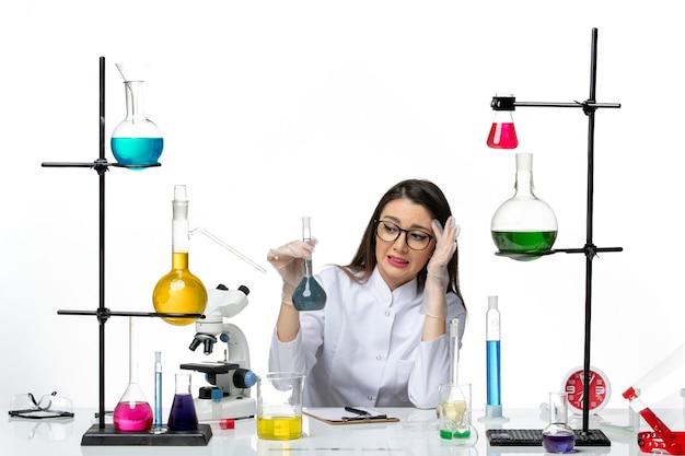 Vooraanzicht vrouwelijke chemicus in wit medisch pak bedrijf kolf met blauwe oplossing op lichte witte achtergrond lab wetenschap virus covid pandemie