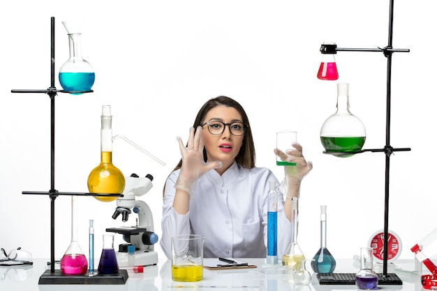 Vooraanzicht vrouwelijke chemicus in wit medisch pak bedrijf kolf met oplossing op lichte witte achtergrond science virus covid pandemie lab