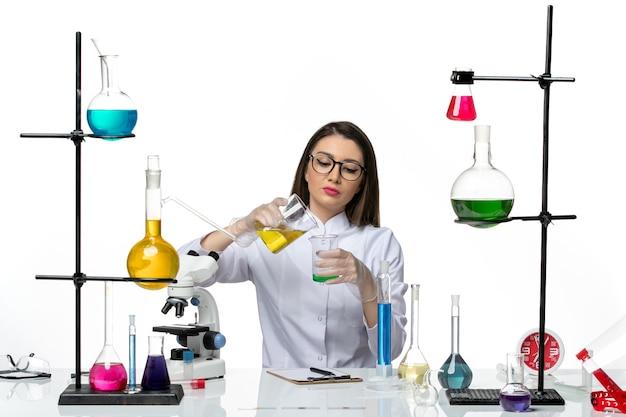 Vooraanzicht vrouwelijke chemicus in wit medisch pak bedrijf kolven met oplossingen op lichte witte achtergrond lab wetenschap virus covid pandemie
