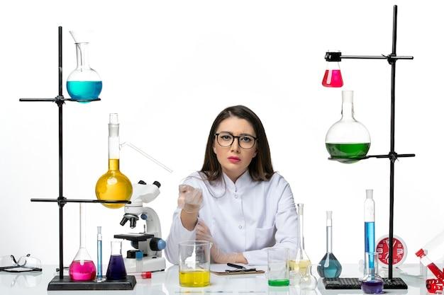 Vooraanzicht vrouwelijke chemicus in wit medisch pak gewoon zittend met oplossingen op lichte witte achtergrond science virus covid-pandemic lab