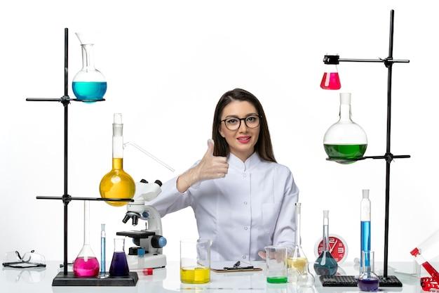 Vooraanzicht vrouwelijke chemicus in wit medisch pak gewoon zittend met oplossingen op lichte witte achtergrond wetenschap covid pandemie lab virus