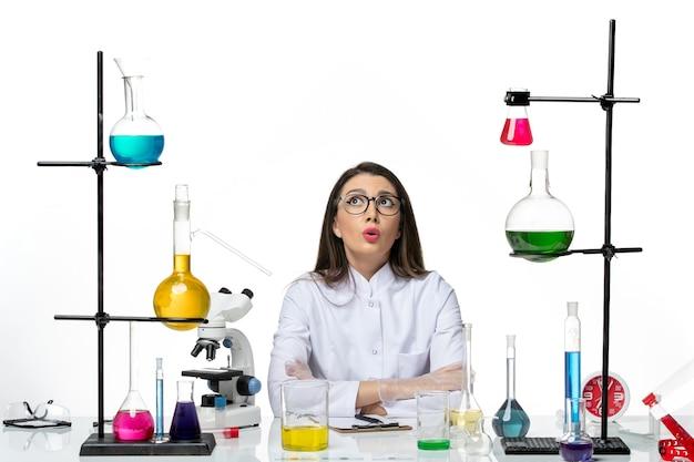 Vooraanzicht vrouwelijke chemicus in wit medisch pak gewoon zittend met oplossingen op witte achtergrond science virus covid-pandemic lab