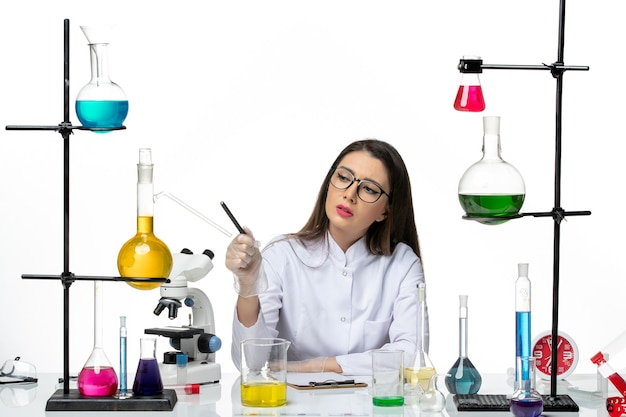 Vooraanzicht vrouwelijke chemicus in wit medisch pak gewoon zittend met oplossingen schrijven van notities op witte achtergrond science virus covid-pandemic lab