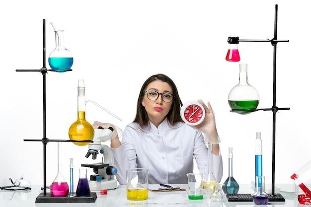 Vooraanzicht vrouwelijke chemicus in wit medisch pak met klokken op lichte witte achtergrond science virus lab covid-pandemie